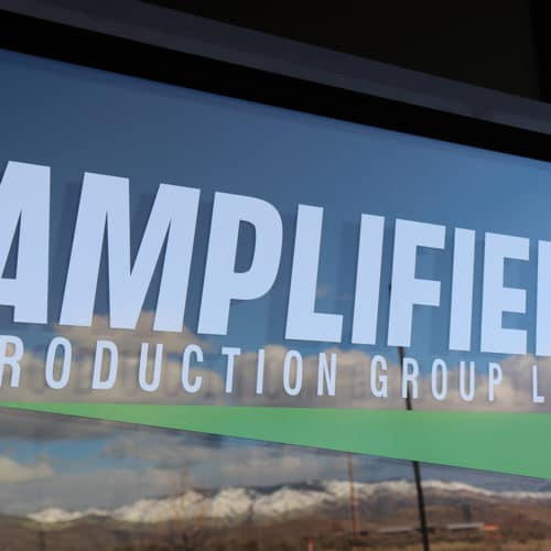 Amplified Production Groups sign on a window featuring a green triangle.